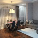 Уютная гостиная с паркетом и рассеянным мягким освещением в ЖК Лыбидь
